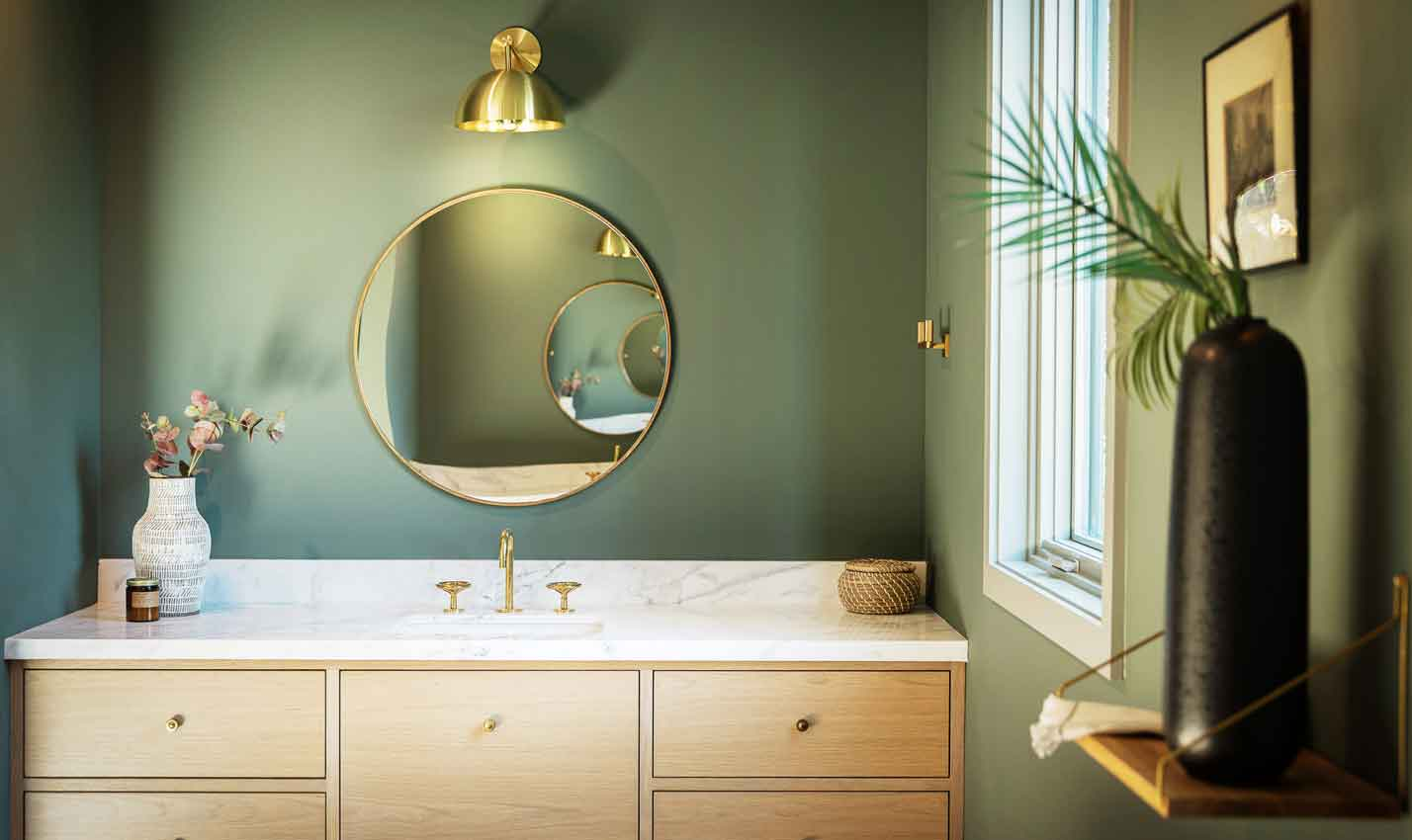A sage green bathroom with marble-top sink/Photography: Watermark Designs/Another moody bathroom, this one designed by Rob Diaz, features soothing sage walls. Experiment with samples like Benjamin Moore's Bonsai and Farrow & Ball's Calke Green.