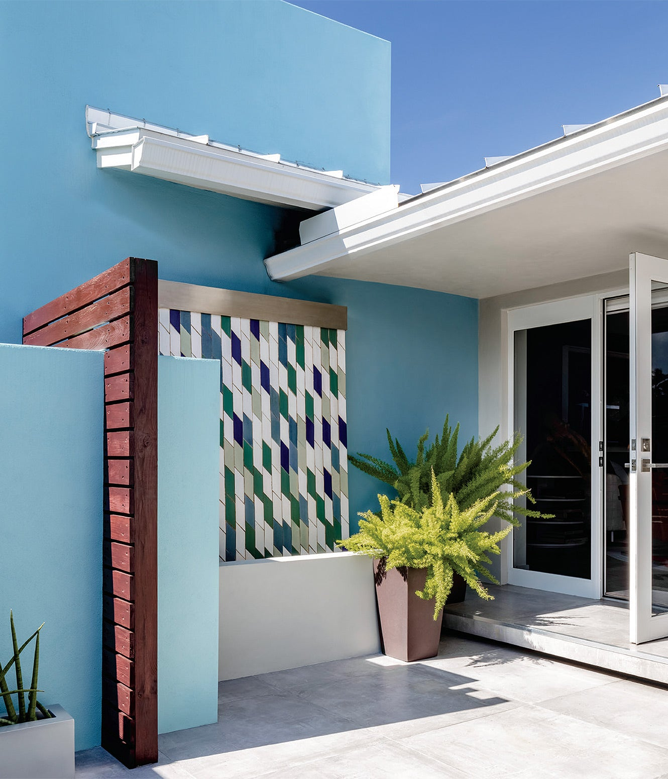 Blue outdoor space with decorative cement tiles/Photographer: Kris Tamburello/Designer Anthony Baratta hewed to a blue color scheme in an indoor-outdoor living space that reflects the sky above this Fort Lauderdale residence.