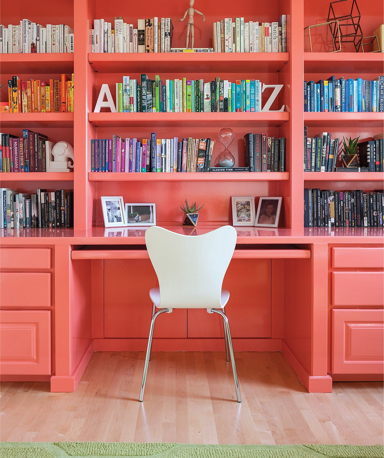 A coral-colored desk and bookshelf with colorful books/Photography: John Granen