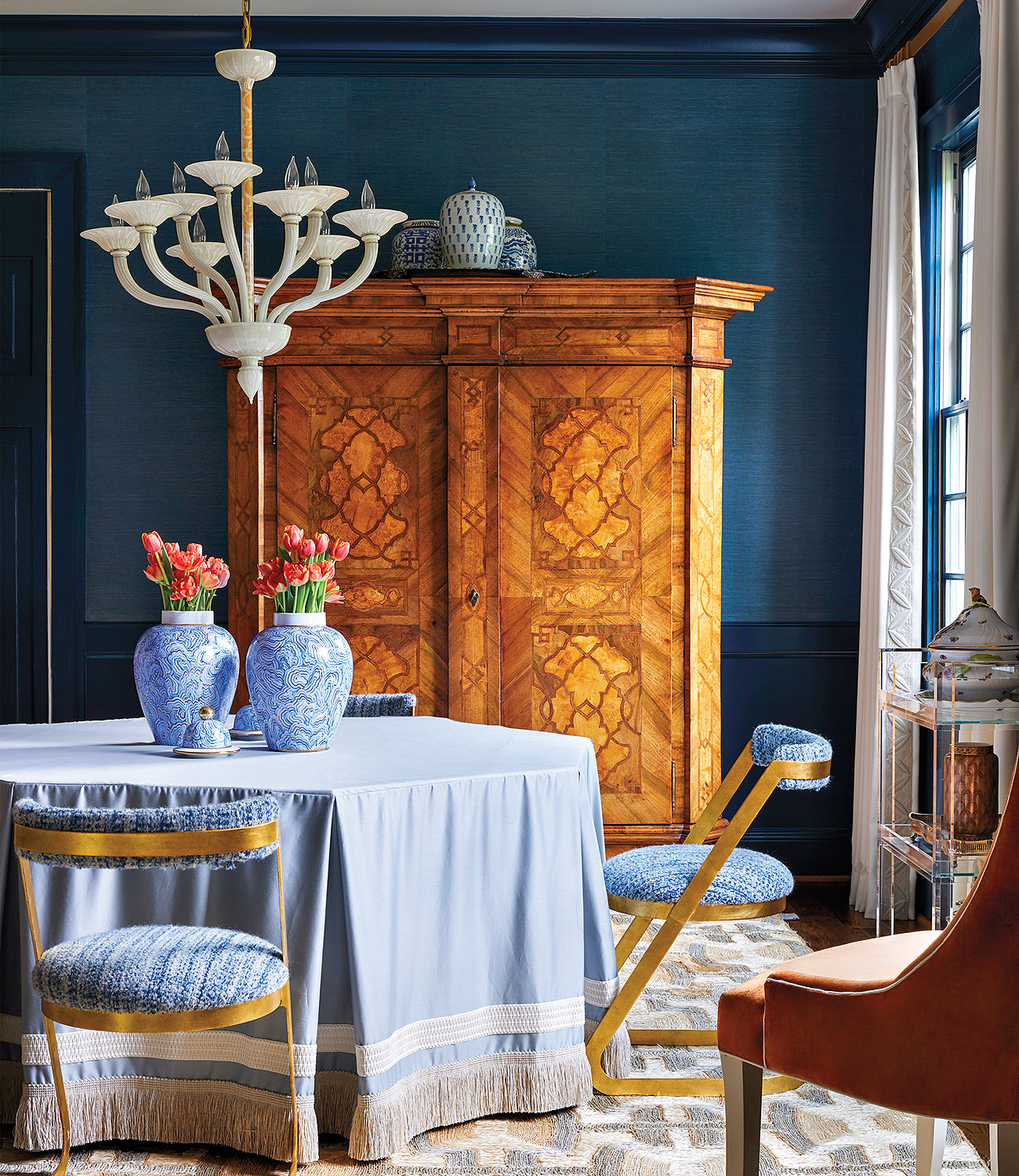 A living room wall painted in Hague Blue/Photographer: Matt Harrington/Designer Blaire Murfree opted for Hague Blue as a complement to a burl-wood armoire and midcentury modern brass chairs in this dining room.