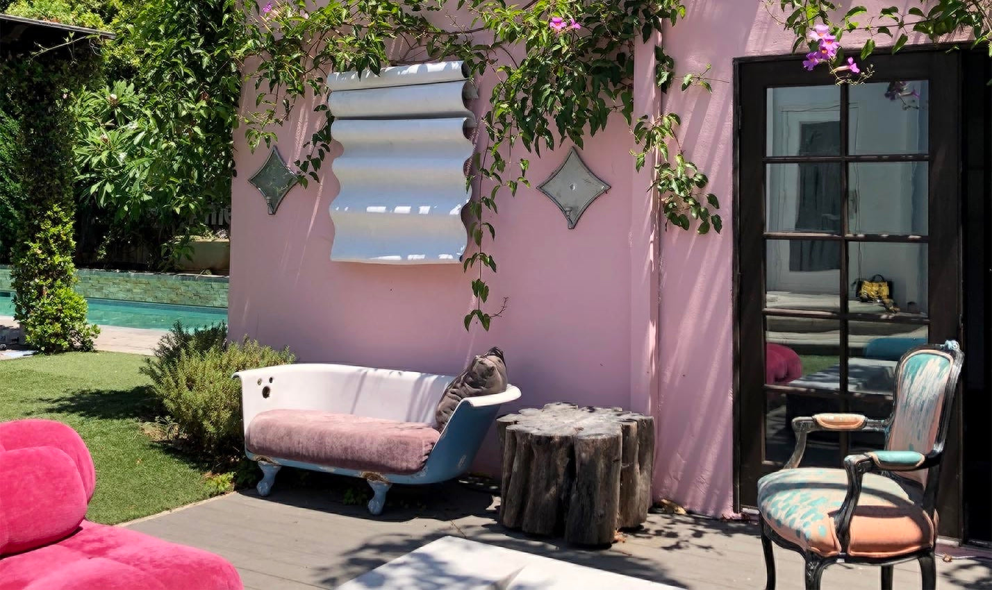 Outdoor area featuring pink background and plants/Courtesy: Voila! Creative Studio/Indoor-outdoor living spaces, like this bright space designed by Voila! Creative Studio, will continue to influence home design.