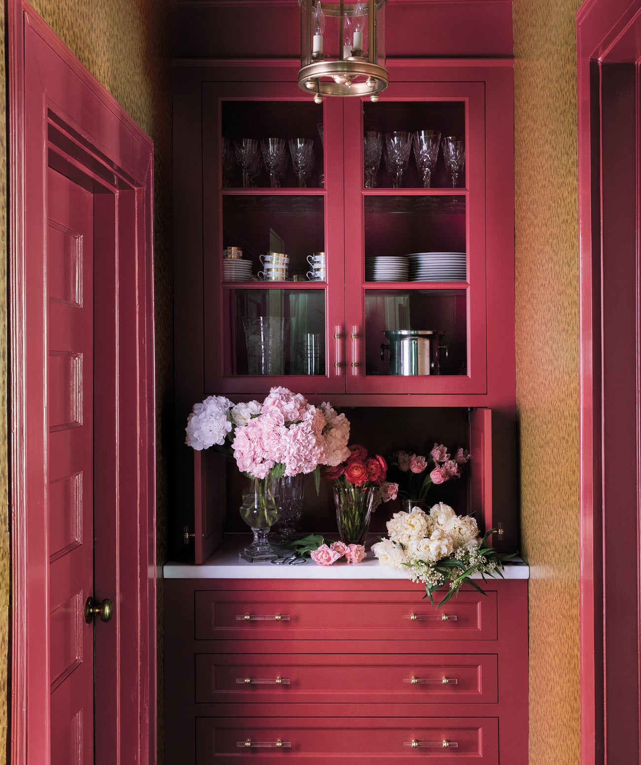 A deep maroon bar area/ Photography: Lesley Unruh/Paint (Benjamin Moore's My Valentine) and wallpaper (Tortoise by Nina Campbell for Osborne & Little) create a cozy bar nook in this home in Bronxville, New York, designed by Sharpe Development and Design.