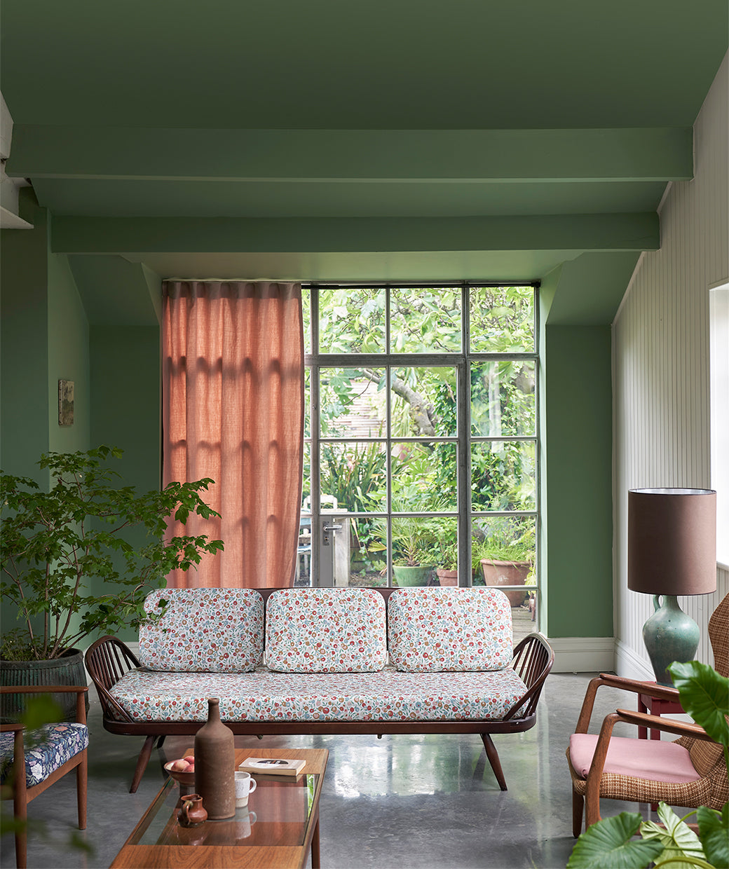 A green sitting room with pale pink drapes/Photography: Farrow & Ball/Farrow & Ball's Suffield Green and Modern Eggshell appear here with Wiltshire Blossom and Emberton Linen designs from Liberty.