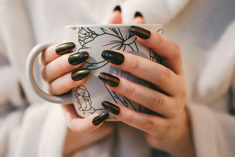 Woman's hands with long green acrylic nails
