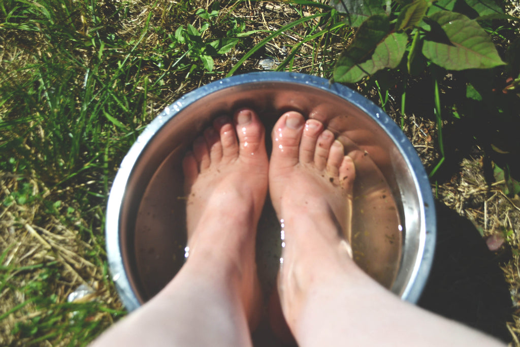 A pair of feet soak in a bowl of cold water with salts mixed in.