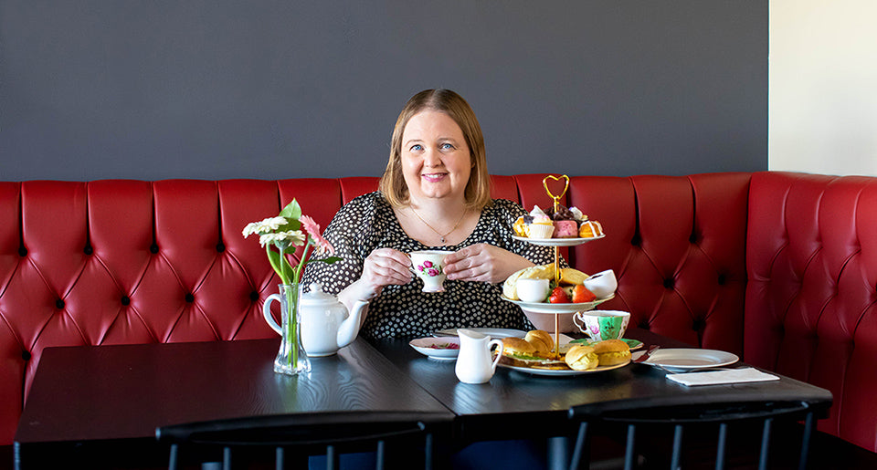 Business Owner, Alyshia, enjoying Afternoon Tea on the red bench at Queen of Hearts Tea House in Kitchener Ontario