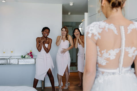 Bridesmsaids looking happy as they meet the bride in a hotel room