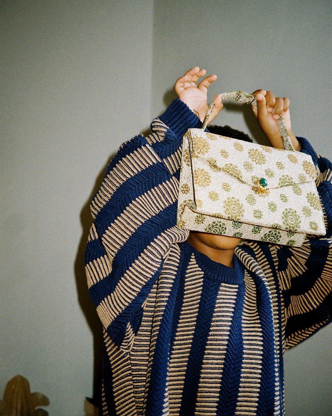 A woman in an oversized blue and yellow sweater holding a patterned gold handbag with a turquoise clasp