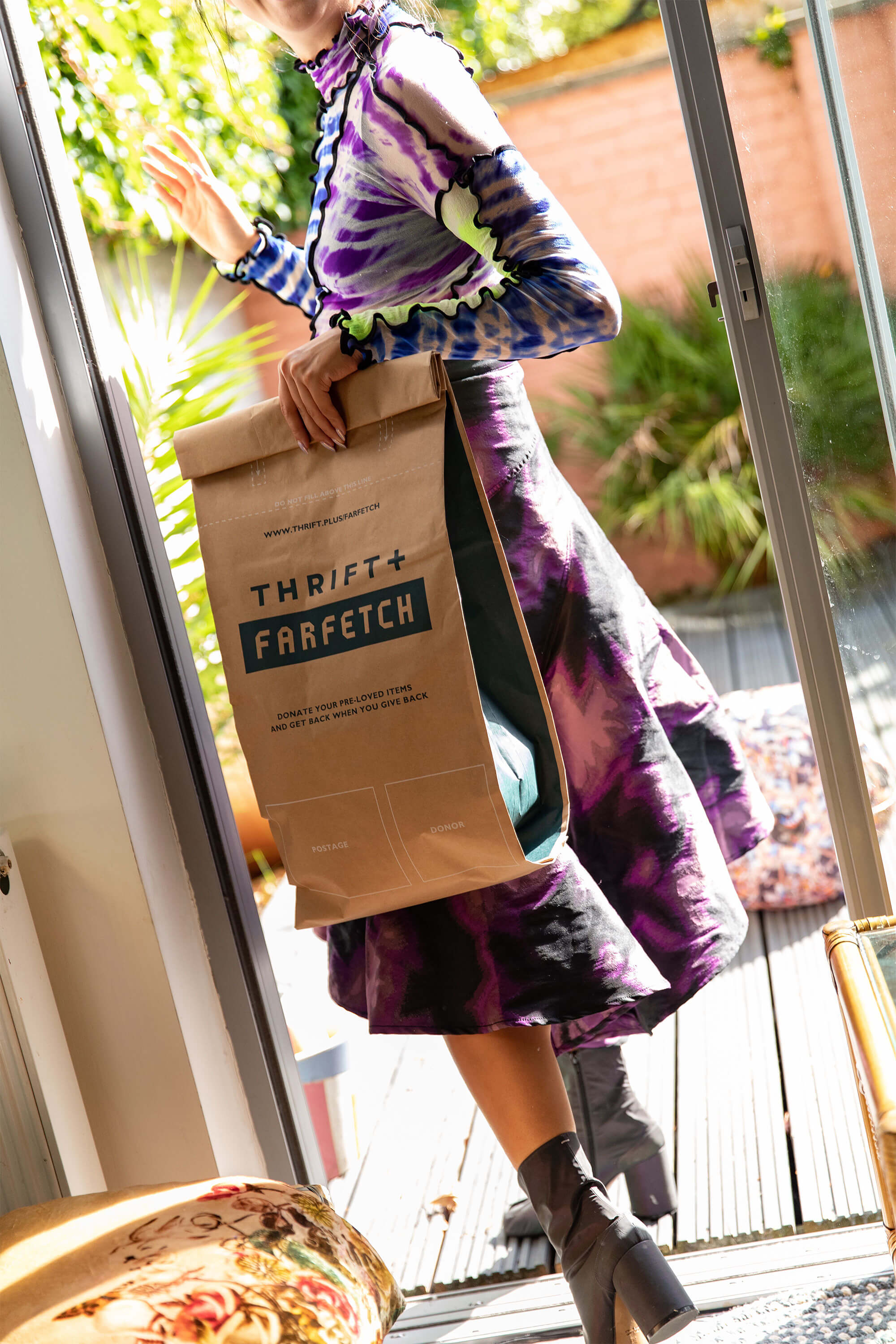 A woman holding a paper bag from Thrift + Farfetch