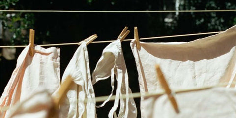 Three thread washing lines with wooden pegs and neutral linen hanging