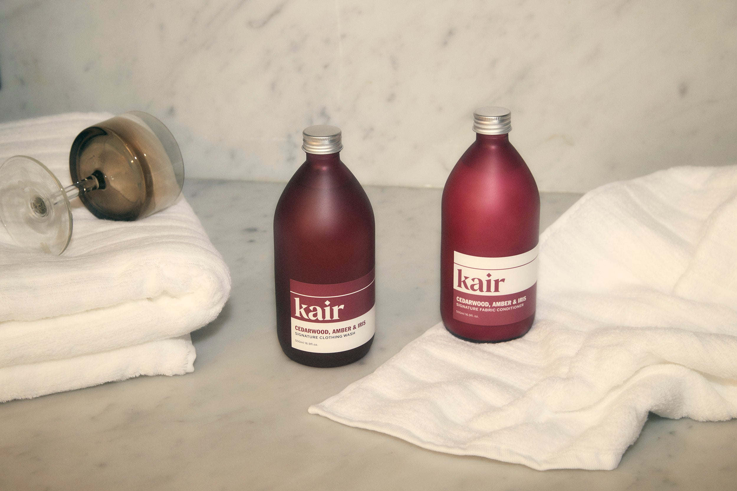 Kair Signature Fabric Conditioner - Cedarwood, Amber & Iris and Wild Juniper & Bergamot positioned among soft towels and a wine glass