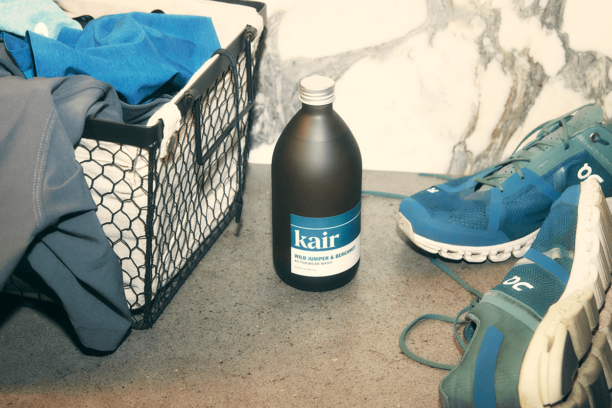 Kair Activewear Wash - Wild Juniper & Bergamot situated next to blue running shoes and a laundry basket filled with activewear