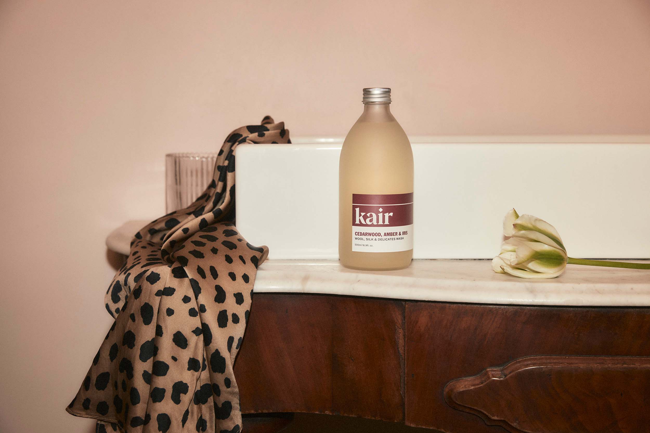 Kair Wool, Silk & Delicates Wash - Cedarwood, Amber & Iris resting on a marble vanity unit next to leopard-print silk fabric and a single rose