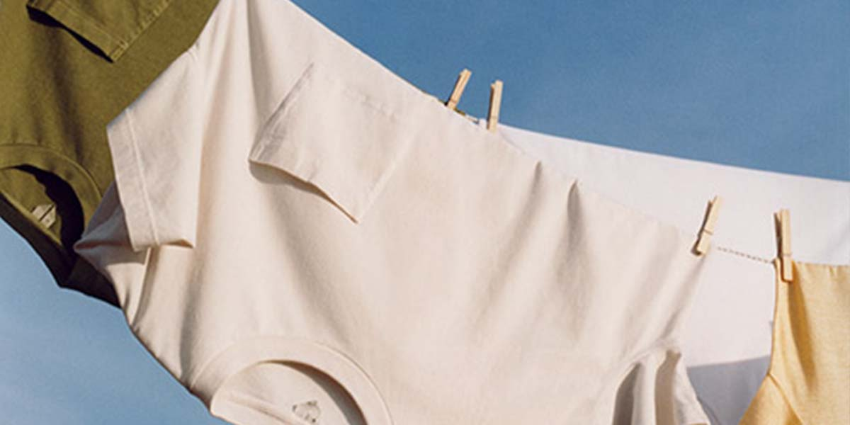 Male T-shirts hanging on a string washing line with wooden pegs. White tshirt, green and yellow