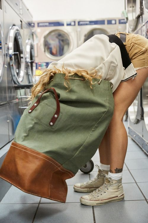 Woman standing in a laundromat with her head inside a large laundry bag