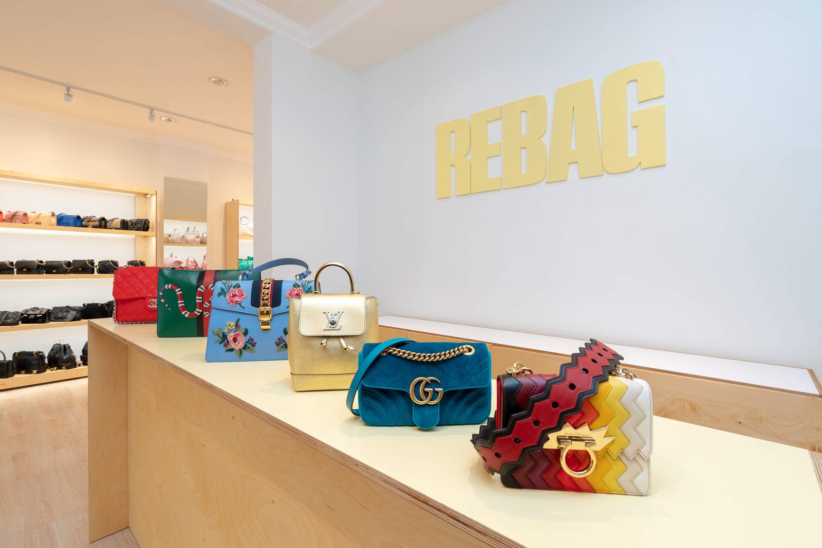 Designer handbags by Gucci, Louis Vuitton and Chanel merchandised in a store setting