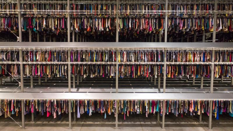 A large number of premium and high-street fashion garments stored in a warehouse setting