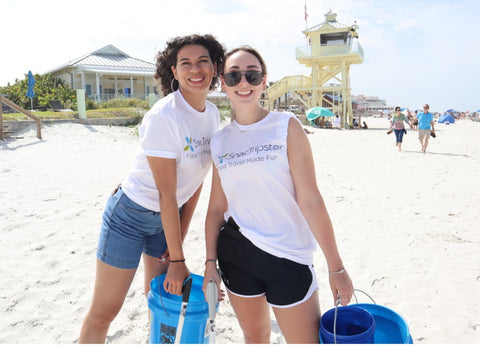 Two team members, Alana (left)  and Gracie (right), hold up the  buckets used to pick up plastic pollution the beach.