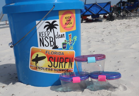 Three BPA free plastic  SnacTripster containers sit next to the bucket used for  SnacTripster's ocean clean  up