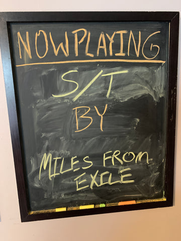 """chalkboard with writing saying """"now playing: s/t by miles from exile"""""""