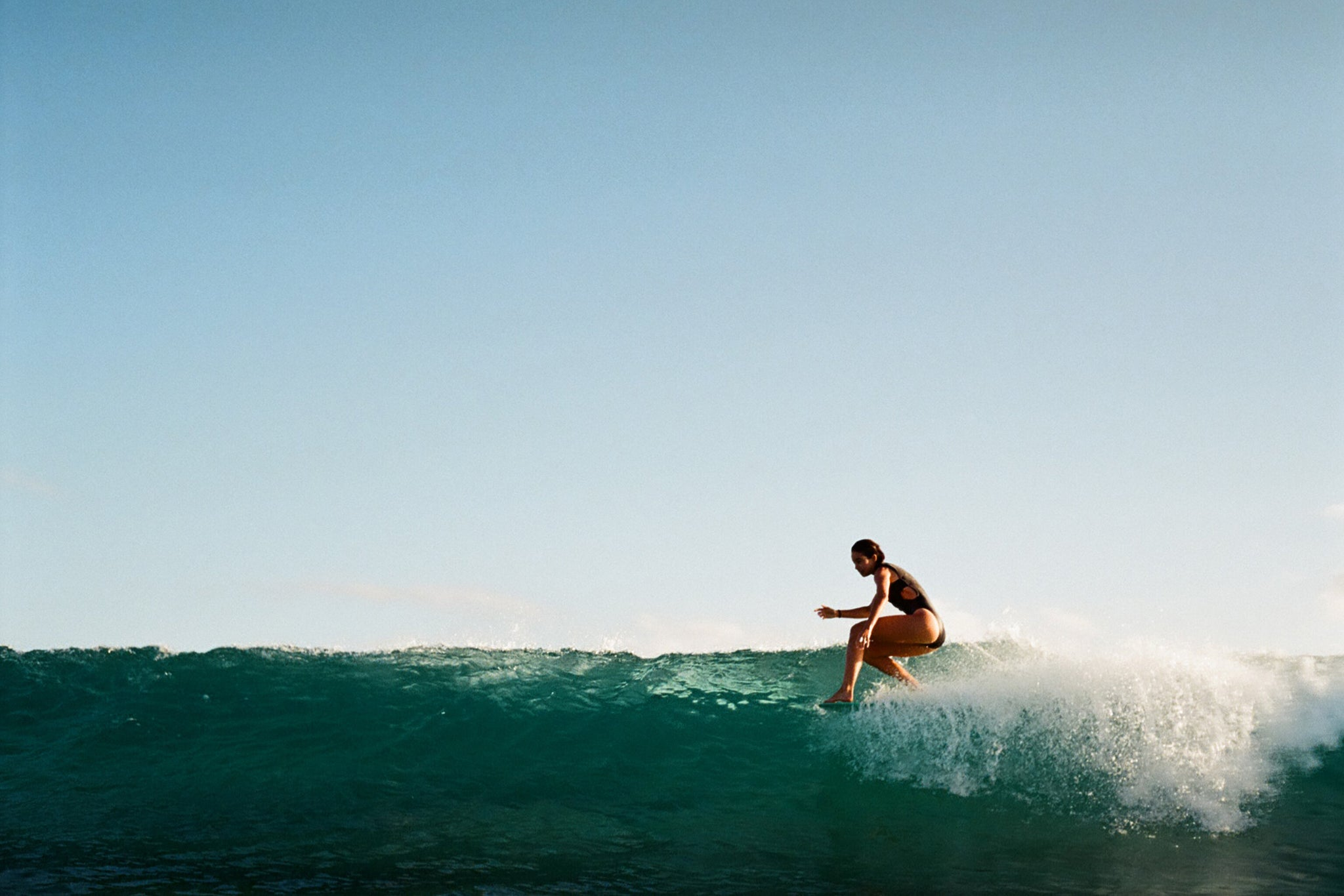 women surfing a perfect wave in black one piece swimsuit