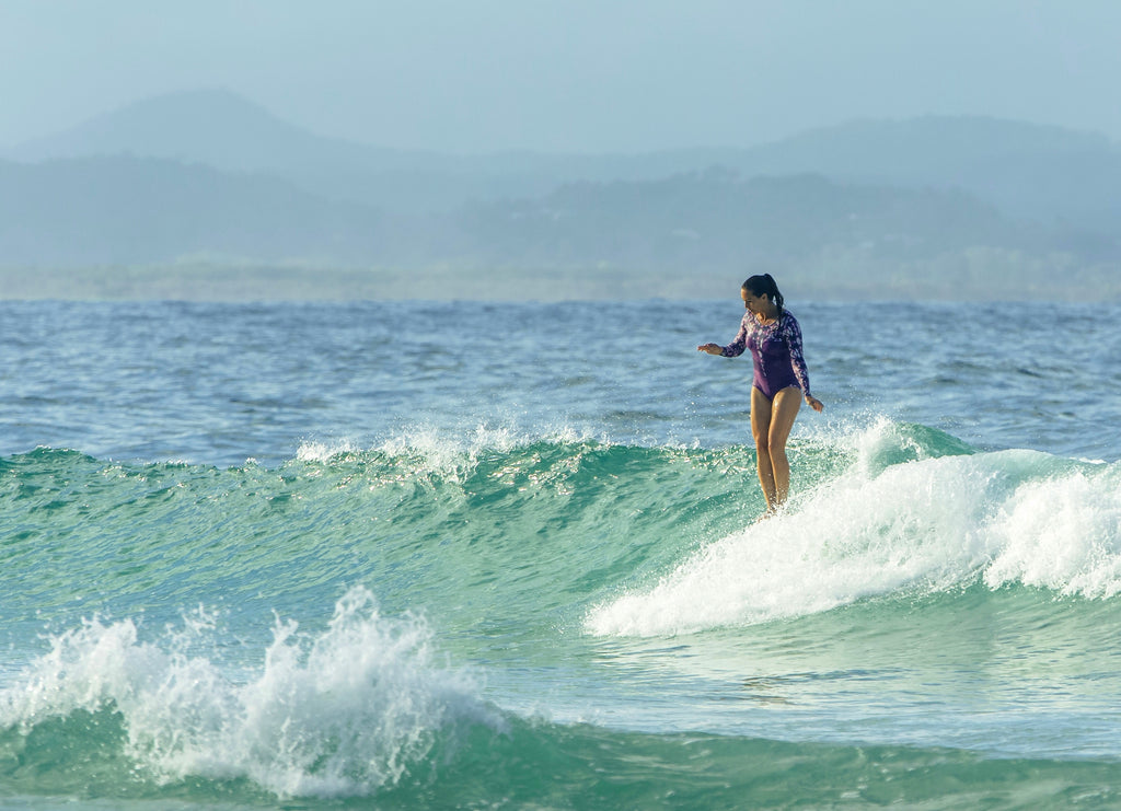 surfer girl hanging ten at The Pass Byron Bay