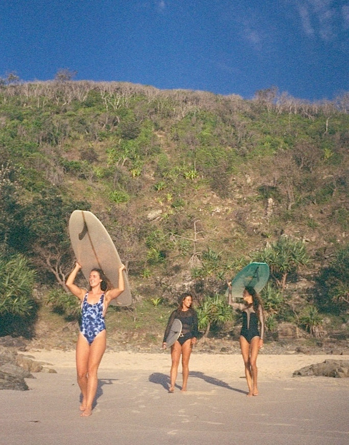 three girls walking with surfboards