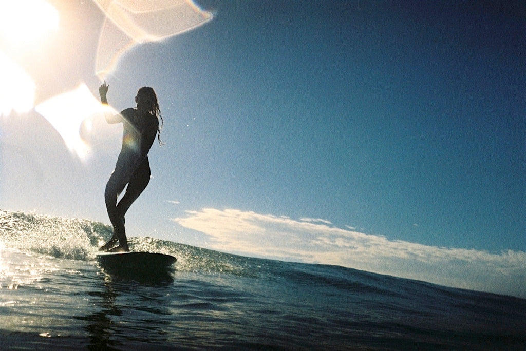Shadow light film photo of a woman surfer