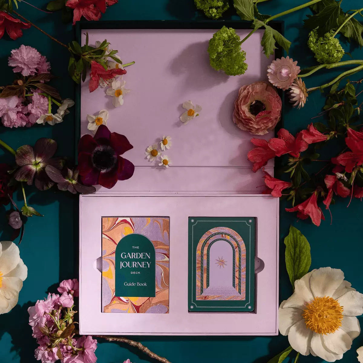 The Garden Journey set lies on a flower-strewn table, showing the booklet and cards.
