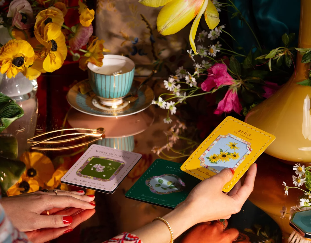 A woman holds up The Garden Journey Deck's Justice card
