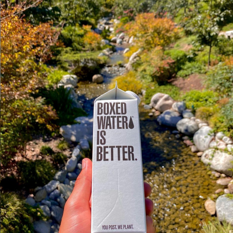 boxed water held out over an autumn garden