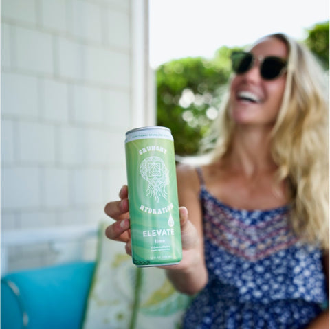 Woman with blonde hair holding Elevate canned sparkling water while laughing