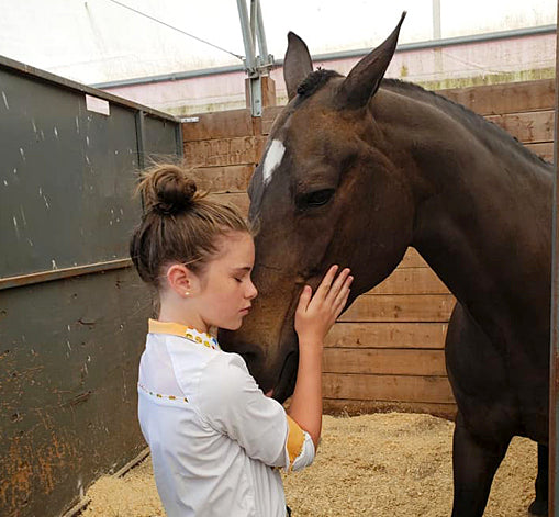 Katie at 11 years old sharing a special moment with her horse Tinker - Red Scarf Equestrian Lifestyle
