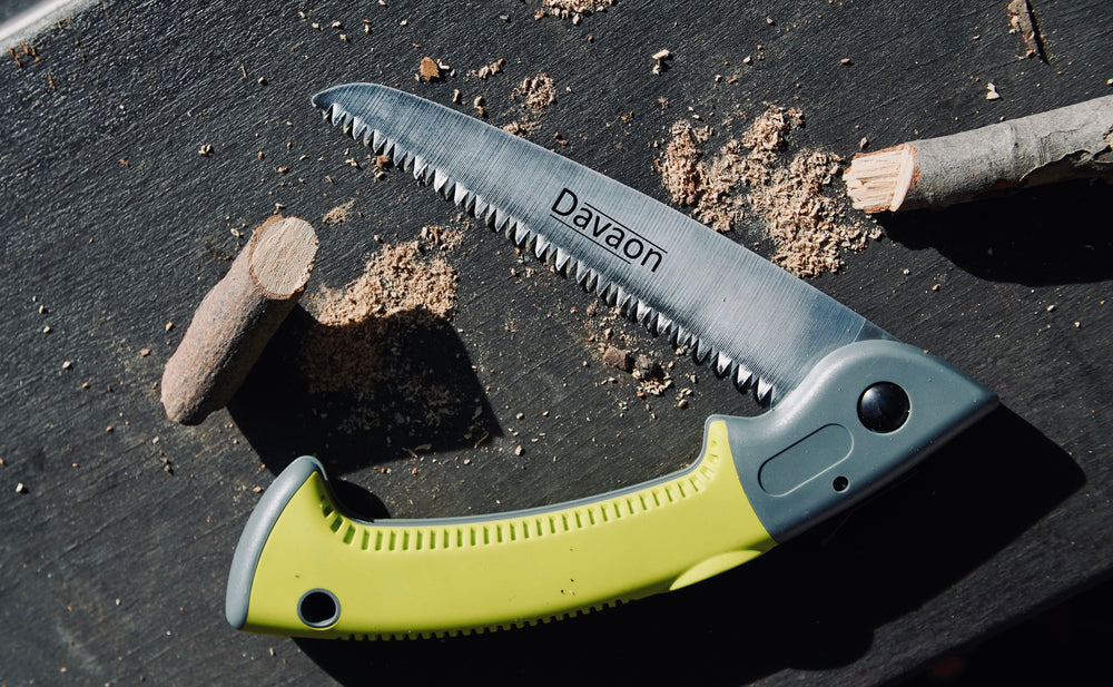 Davaon's premium folding saw on a dark, textured background. The hand saw is depicted as having just cut through a branch. It is half-folded.