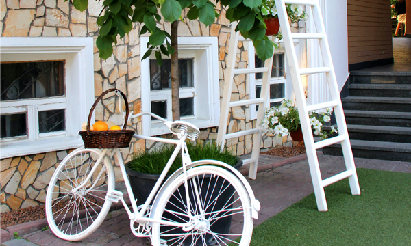summer patio with hanging flower pots and a white bicycle leaning against a tree