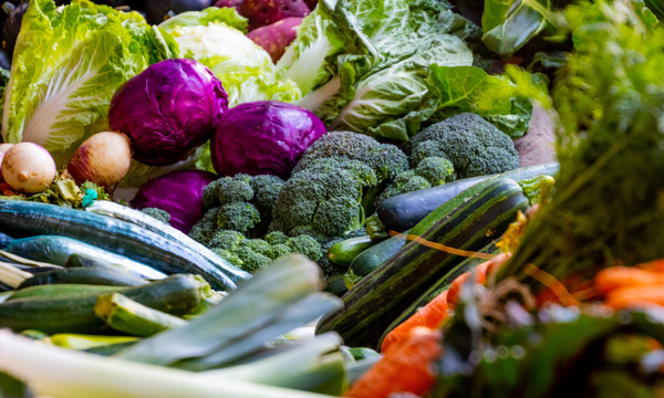 a basket full of vegetables including broccoli, red cabbage, cucumber, leek, and zucchini