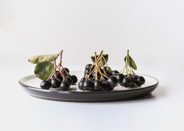 Aronia berries on top of small white plate