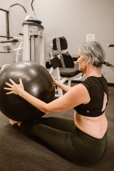Middle aged woman in the gym exercising with a black yoga ball