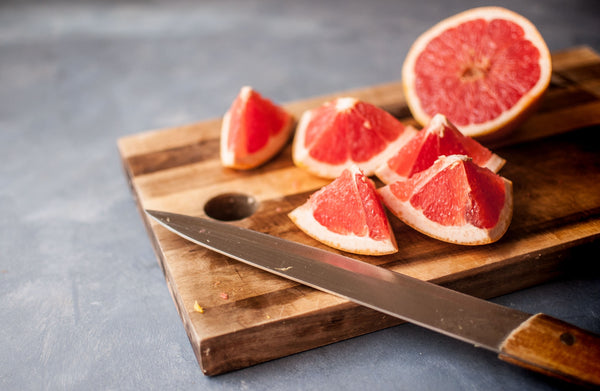 sliced grapefruit on wooden chopping board