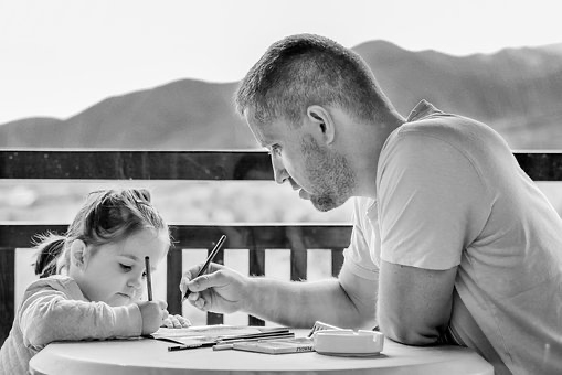black and white photo of dad teaching daughter to wrote