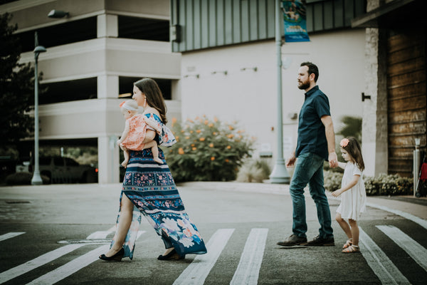 young parents with their kids crossing the street