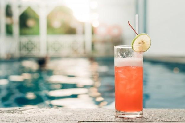 fruity ginseng punch in a glass with a swimming pool background