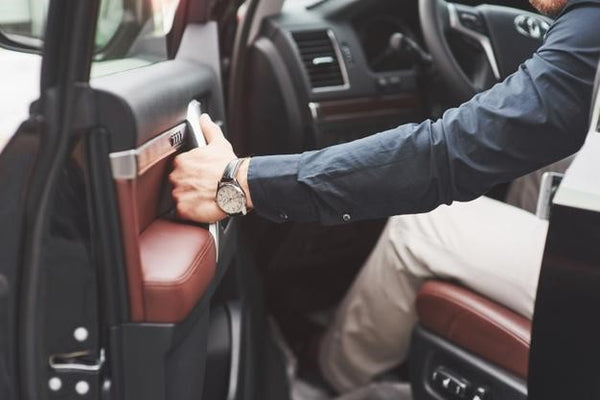 man wearing watch about to close car door