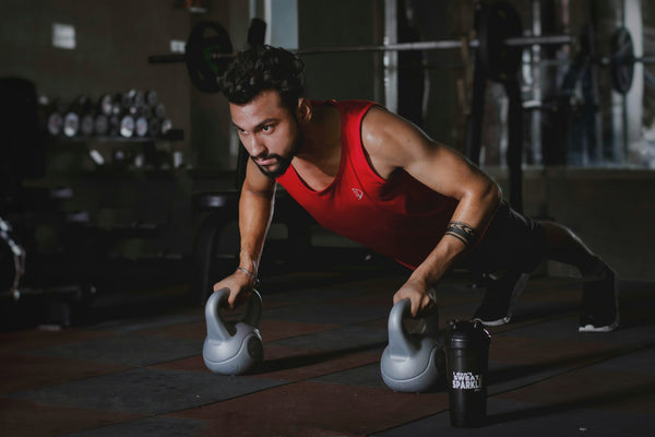 man wearing red muscle shirt working out in the gym