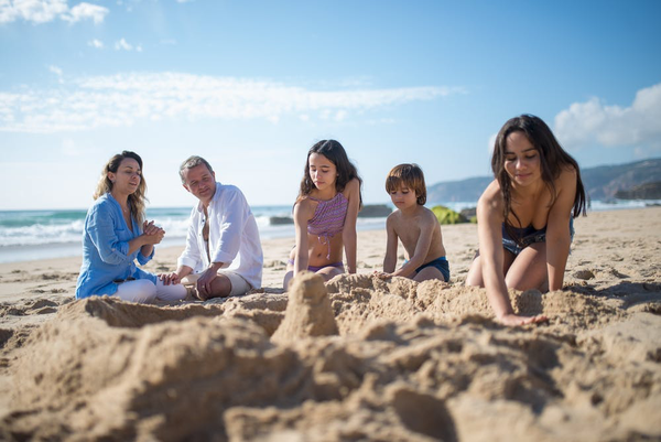 parents with three kids playing on the beach.png