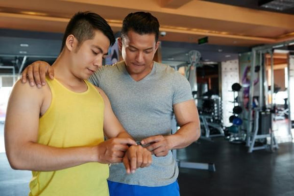 two men checking out fitbit watch inside a gym