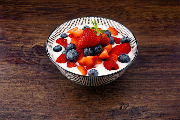 bowl of yogurt with berries on wooden table