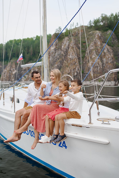 young family of four laughing while sitting on yacht