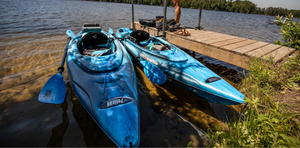 Two blue MISSION100 kayaks with paddles by a dock on a lake