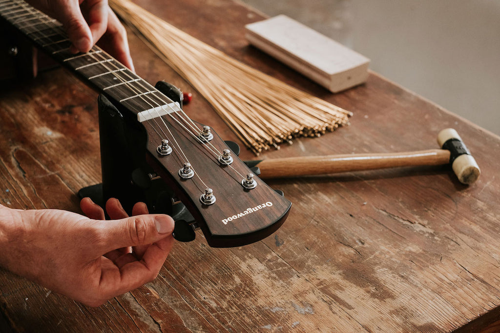 Technician sets up Orangewood guitar on a rustic workbench.